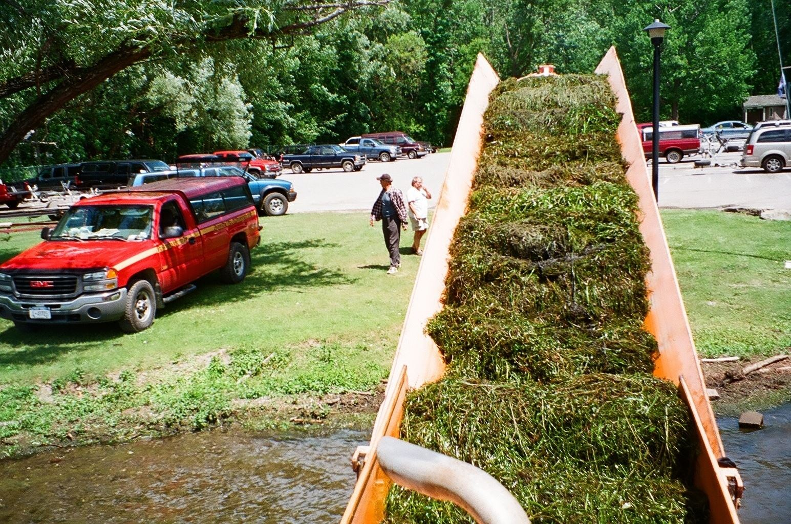 Aquatic weeds being transported from harvester to truck by conveyor, Honeoye Lake